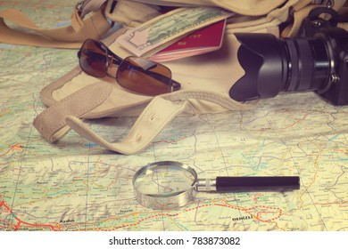 trraveller's set on open map - soft bag, passport, money, sunglasses and photo camera, toned