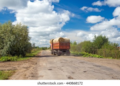 truck with bales of hay rides on the road