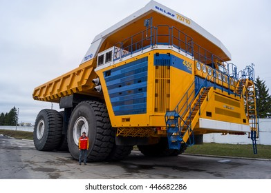 Truck BelAZ with man for scale. Yellow coloring huge mining haul truck. Zodzina, Belarus - March 9, 2016: Haul truck BelAZ 75710 by Belarusian manufacturer BelAZ with man for scale.