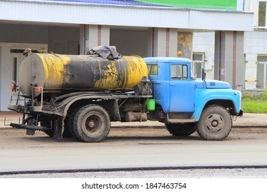 A truck with a blue cab with a yellow tank to transport molten bitumen. Road equipment on the street of the city in Russia. Repair work on the road in the spring.