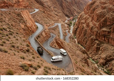 Truck and campervans climbing up the winding roads of the Dades gorge pass in Morocco.