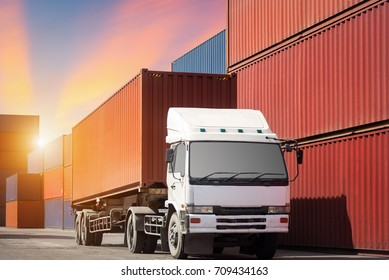 truck with cargo container on road in shipping yard or dock yard against sunrise