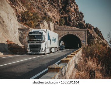 Truck carrying freight on a mountain road, at the exit of a tunnel. Autumn landscape. This is a VOLVO OCEAN RACE truck. Belongs to the German company S&G Logistik. Romania, Severin, October 29, 2019