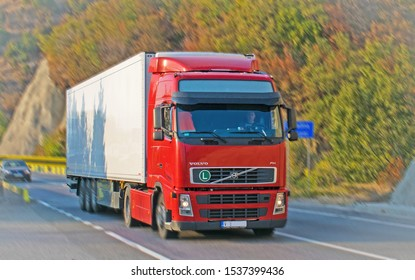 truck carrying goods - this is VOLVO. The truck has a red cab and is in motion.Pannig effect. A beautiful autumn landscape. Location: Romania, Orsova. October, 20, 2019