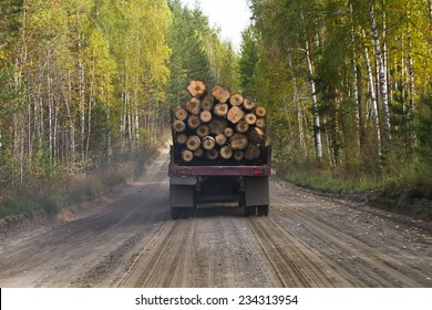 truck carrying wood on a dirt road