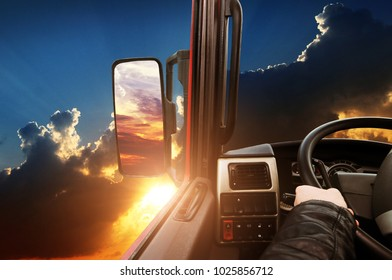 Truck dashboard with driver's hand on the steering wheel and side rear-view mirror against night sky with sunset