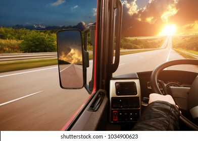Truck dashboard with driver's hand on the steering wheel and side rear-view mirror on the countryside road against night sky with sunset