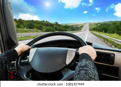 Truck dashboard with driver's hand on the steering wheel on the countryside road against blue sky with sun