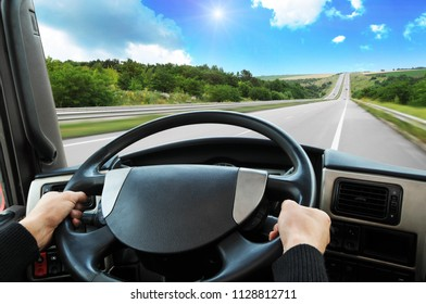 Truck dashboard with driver's hands on the steering wheel on the countryside road against blue sky with sun