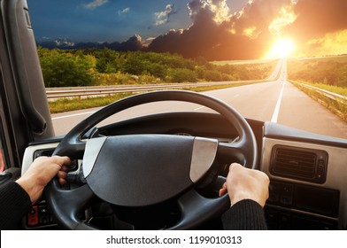 Truck dashboard with driver's hands on the steering wheel on the countryside road against night sky with sunset