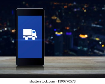 Truck delivery flat icon on modern smart mobile phone screen on wooden table over blur colorful night light city tower and skyscraper, Business transportation online concept