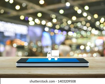 Truck delivery flat icon on modern smart mobile phone screen on wooden table over blur light and shadow of shopping mall, Business transportation online concept