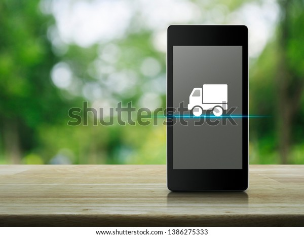 Truck delivery flat icon on modern smart mobile phone screen on wooden table over blur green tree in park, Business transportation online concept