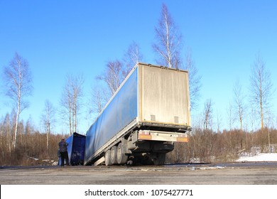 The truck in the ditch – crash, skid, black ice, accidents in the winter on the background of the road, trees and blue clear sky. The driver is talking on the phone.
