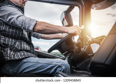 Truck Driver Behind the Wheel. Semi Truck Driving and Transportation Industry.