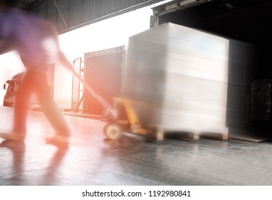 Truck driver dragging hand pallet, unloading the shipment pallet at docks in warehouse.