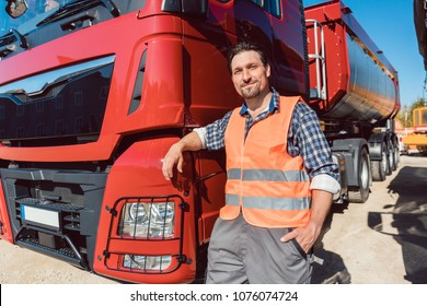Truck driver in front of his freight forward lorry looking at camera