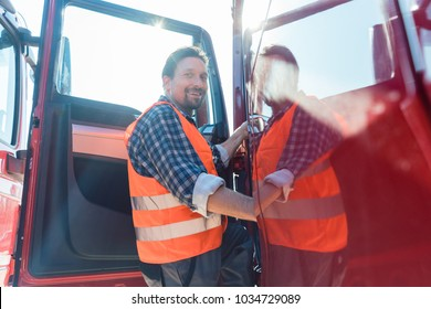 Truck driver in front of his long haul lorry getting in