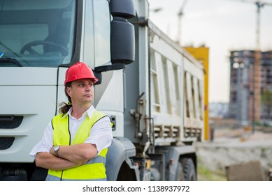 Truck driver in front of a truck on a construction site with his arms crossed