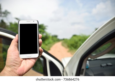 Truck driver holding smart phone with blank screen on dirt road into the wilderness, GPRS navigation or finding phone signal conceptual