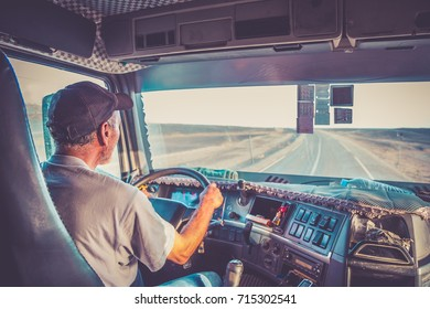 The truck driver is holding the steering wheel and is driving a truck on the long highway. Empty bright road is ahead of him.