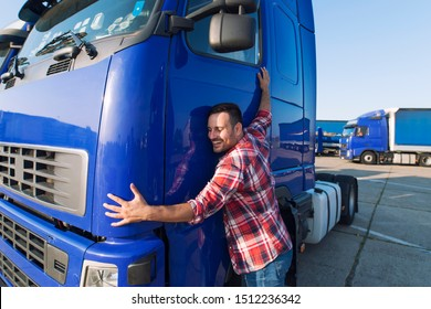 Truck driver loves his job. Professional trucker driver hugging his truck cabin loving his job.