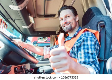Truck driver man sitting in cabin giving thumbs-up
