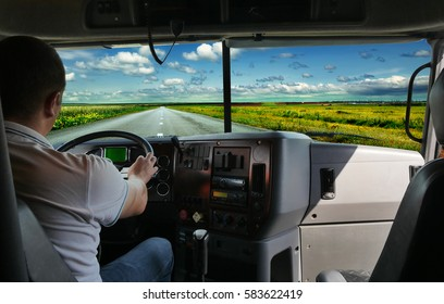 The truck driver on the road among fields highway. business trip