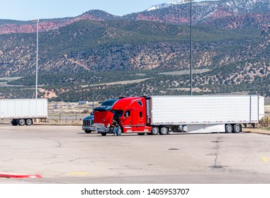 Truck driver repairing Broken American industrial grade freight transportation red big rig semi truck tractor with an open hood stands on the truck stop parking lot trying to repair truck on site