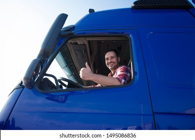 Truck driver showing thumbs up through cabin window. Positive smiling trucker ready for a new ride. Transportation services.