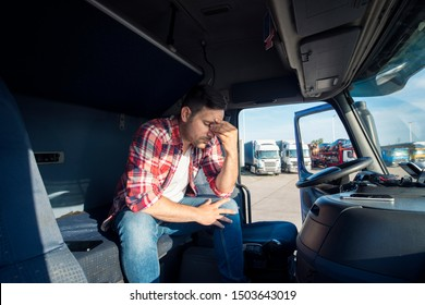 Truck driver sitting in his truck cabin feeling worried and upset. Truck driver lifestyle and problems.