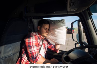Truck driver sleeping in cabin of his truck due to driving long distances and overworking. Trucker lifestyle.