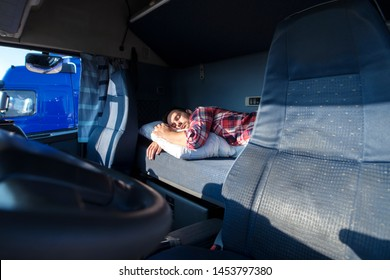 Truck driver sleeping on bed inside truck cabin interior. Trucker lifestyle.