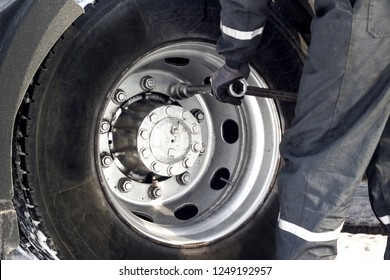 Truck driver using wrench for tyre repair.