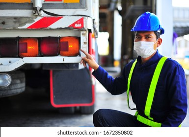 Truck driver wearing blue safety helmet with protection mask pointing finger to truck taillight.