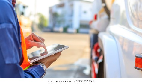 Truck drivers hand holding tablet checking the product list,Driver writing electronic log books,spot focus.