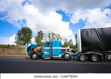 Truck drivers repairing big rig blue bonnet semi truck with open hood breakage occurred during the delivery of the goods and carry covered loaded semi trailer stand right on the road shoulder side