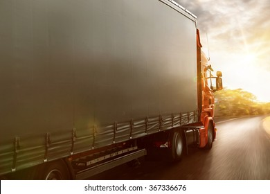 Truck drives on a country road at sunset