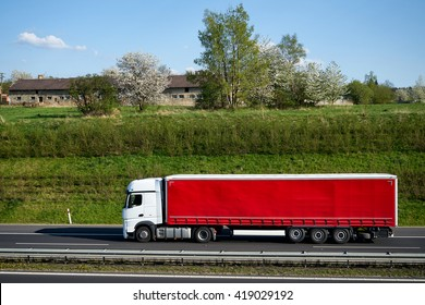 Truck driving on asphalt highway beneath the green grassy slope. Flowering trees, village and old farm building on the horizon. Sunny spring day with blue skies and white clouds.
