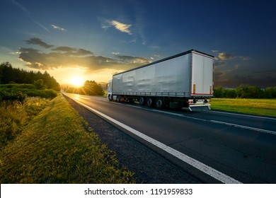 Truck driving on the asphalt road in rural landscape at sunset