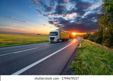 Truck driving on the asphalt road in rural landscape in the rays of the sunset with dark storm cloud