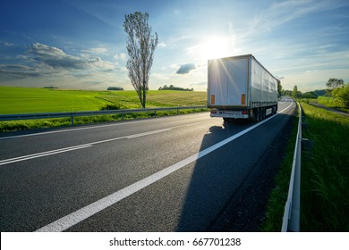 Truck driving on asphalt road along the green fields in rural landscape at sunset