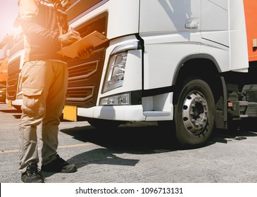 Truck driving safety, Truck driver holding clipboard with checking maintenance program of a truck
