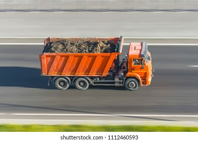 Truck dump with a load of soil in the body rides at high speed on the highway