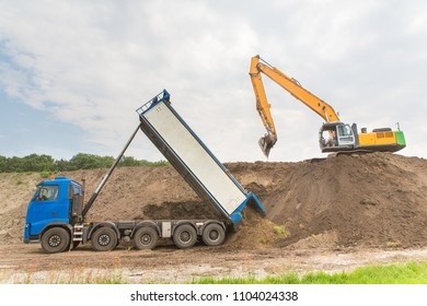 Truck and excavator together build a sound barrier of sand