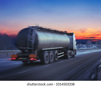 Truck with the fuel on winter highway at sunset