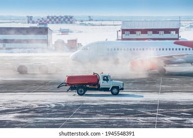 A truck with fuel or water rides on the taxiway at the airport against the background of a smoking plane in winter. Concept of a dangerous incident and fire or engine failure