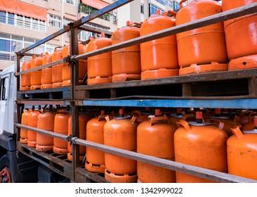 Truck full of orange gas cylinders transporting butane