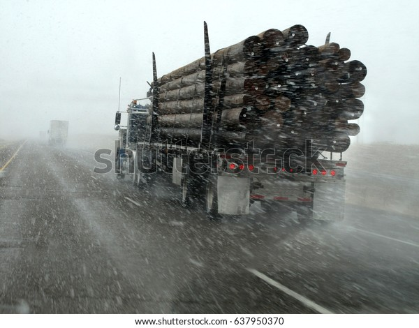 Truck hauling wood driving in snow storm