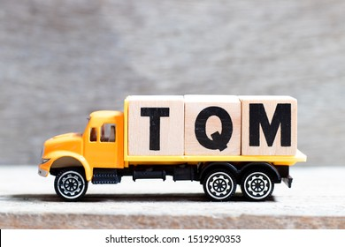 Truck hold letter block in word TQM (Abbreviation of total quality management) on wood background
